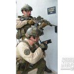 Two KSP SRT members check around a corner.