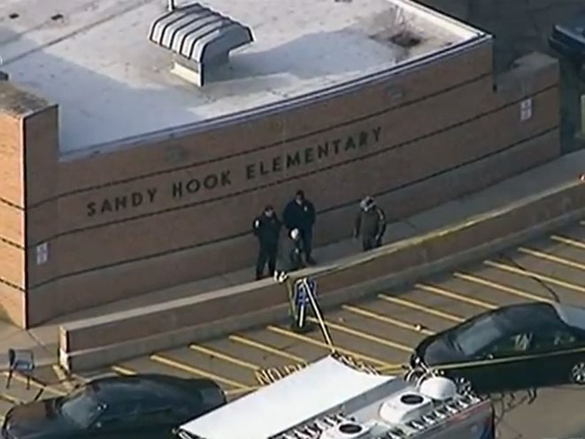 Police arrive in front of Sandy Hook Elementary School after the shooting.