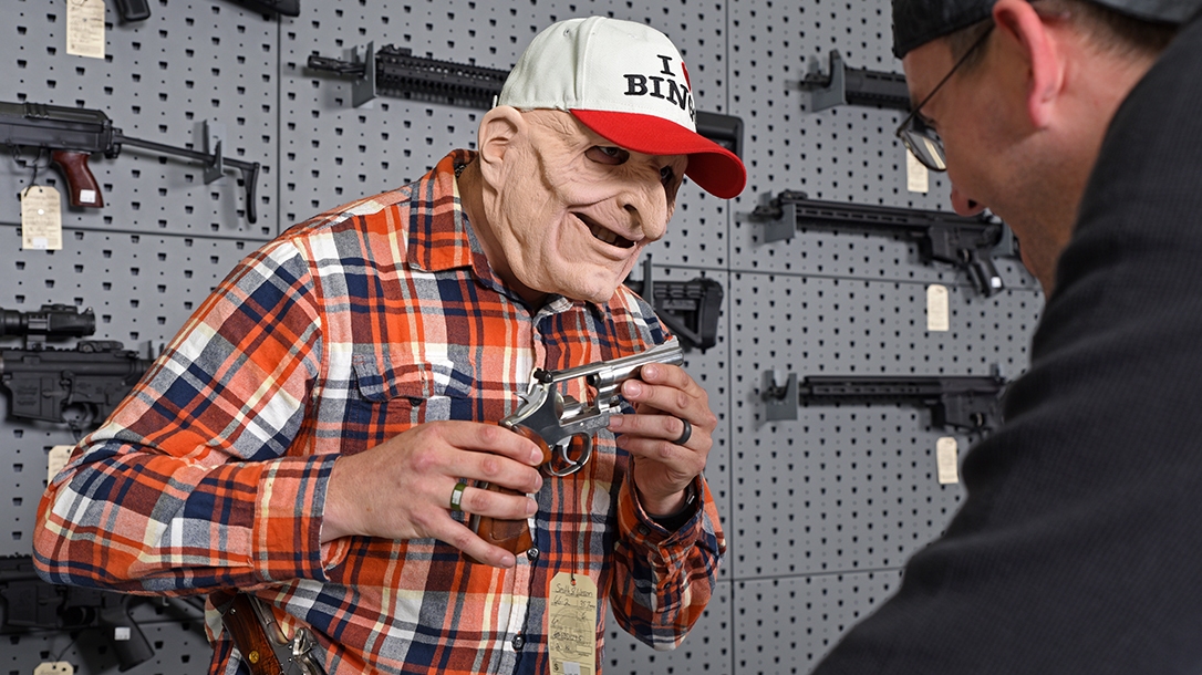 The old guy is just that, the elder statesman, most likely holding something wood and blue, and a 1911.