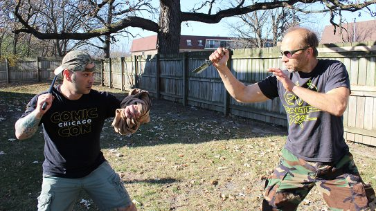 The author uses a wrapped jacket around his arm to protect himself from being cut. He uses a fighting stick as an equalizer for knife defense.